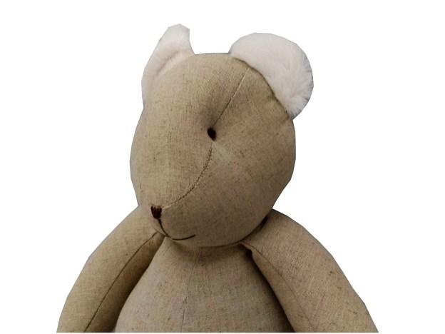 urso teddy de pano bege com detalhes em pelúcia branca