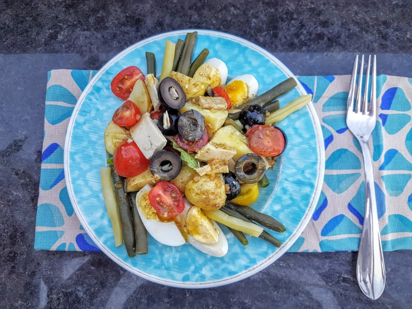 Blue salad plate with arranged nicoise salad