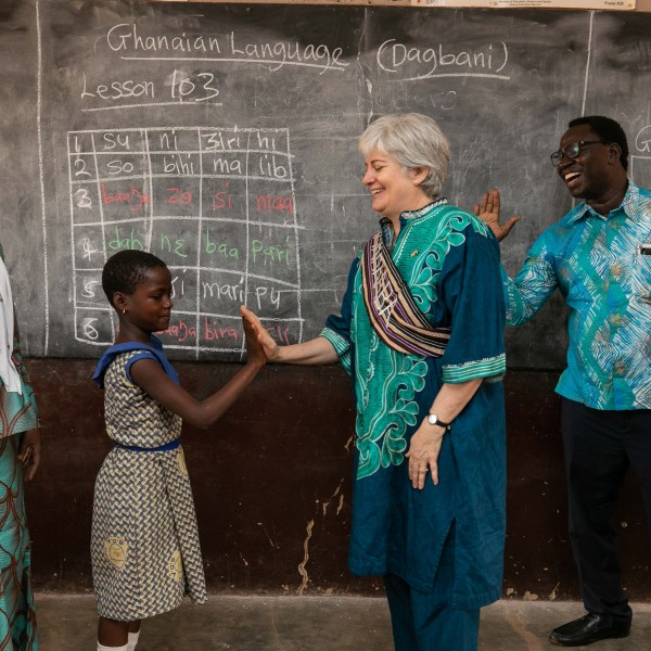 Woman in traditional clothes high fives a young girl in front of Ghanian lessons