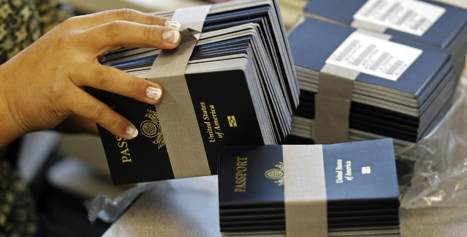 A State Department employee processes stacks of passport books at the New Orleans Passport Agency.