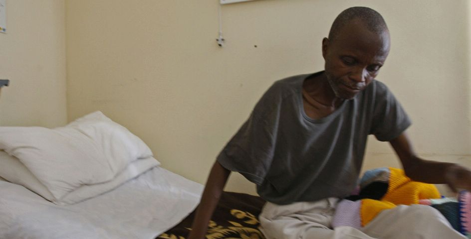 A man slowly rises from his bed at the Baphumelele Center, a treatment ward for people affected by AIDS on the outskirts of Cape Town, South Africa.
