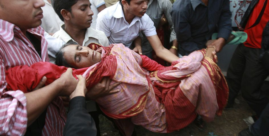 Sufia Begum, 50, faints while waiting for news of her daughter Razia Akter, a garment worker missing in a factory fire in Ashulia, Bangladesh.