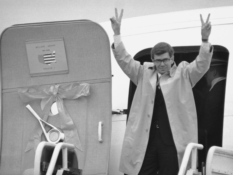 Freed hostage Bruce Laingen makes ?V? signs as he steps from the first of four planes carrying the freed hostages from West Point, N.Y., to their official welcome in Washington on Tuesday, Jan. 27, 1981 at Andrews Air Force Base in Maryland. Laingen was the charge d?affaires of the U.S. Embassy in Iran.