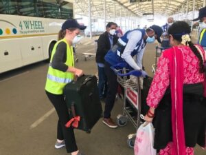 U.S. Consulate General Hyderabad staff help travelers load luggage at the airport.