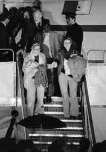 Kathryn Koob, right, and Elizabeth Ann Swift hold hands as they leave the Algerian aircraft which brought them to Algiers from Tehran at Algiers airport, Jan. 21, 1981. The women were two of the United States hostages held for 444 days in Iran. Others are unidentified.