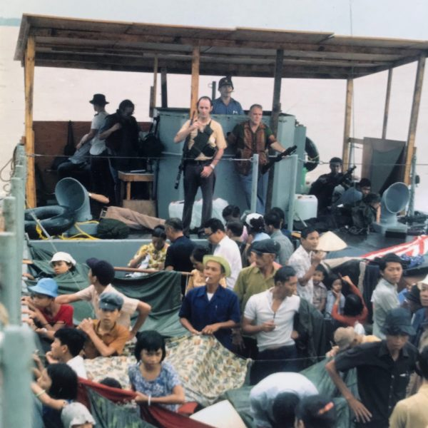 Consul General Francis Terry McNamara (behind the two armed guards) captains a barge of American and Vietnamese refugees out of Cần Thơ. Photo Courtesy of the National Museum of American Diplomacy.