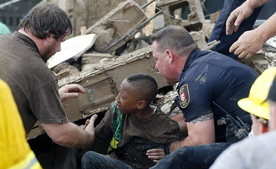 A boy is pulled from beneath a collapsed wall at the Plaza Towers Elementary SchoolCredit: AP