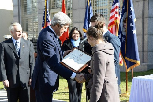 U.S. Secretary of State John Kerry presents an award to the family of Embassy guard Mustafa Akarsu at a Memorial Ceremony at the U.S. Embassy in Ankara, Turkey, on March 1, 2013. [State Department photo/ Public Domain]