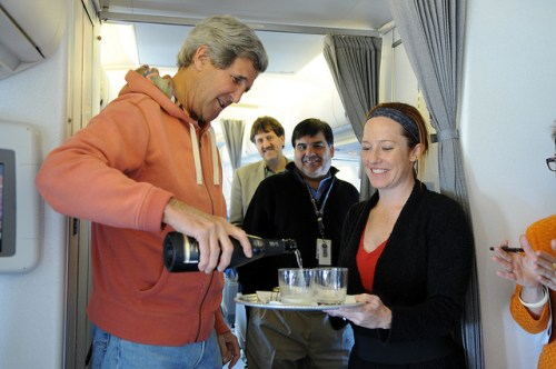 U.S. Secretary of State John Kerry uncorks a bottle of champagne en route from Andrews Air Force Base to Stockholm, Sweden as he celebrates the first press briefing at the U.S. Department of State Department by his new Spokesperson, Jen Psaki, on May 13, 2013. [State Department photo / Public Domain]
