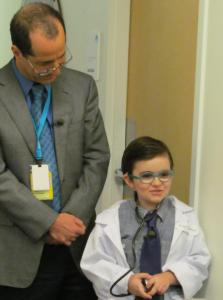 Photo of a tall man in glasses wearing a tie looking down at a young boy wearing play glasses, a tie, a white coat, and a stethoscope.