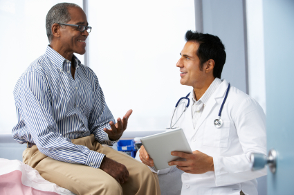 Doctor with an iPad-type device talking with a patient