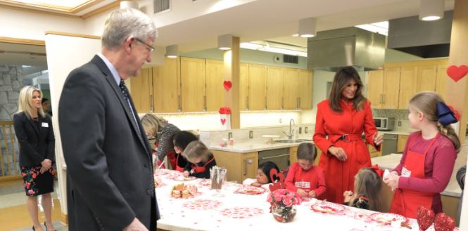 Francis Collins watches Melania Trump interact with children
