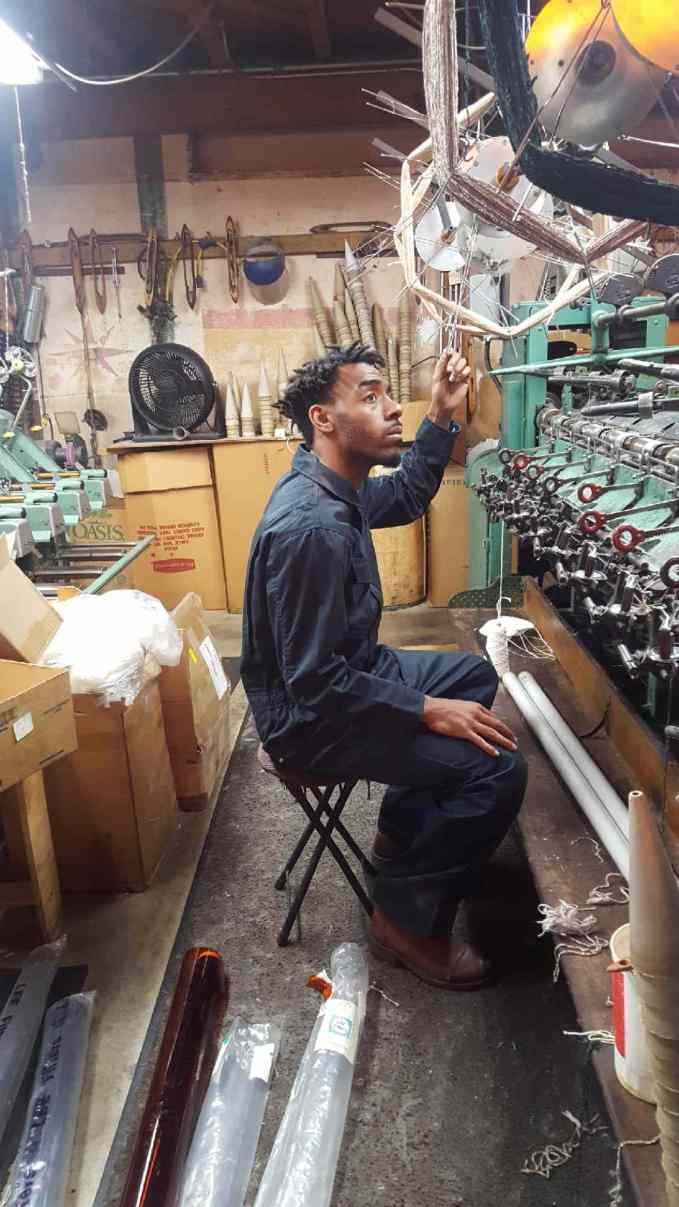 "Jamar ""Soup"" Campbell examines the factory threading machines that will be a part of the dance climax."