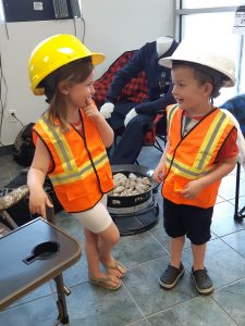 Two children in orange hi viz safety vests and hardhats