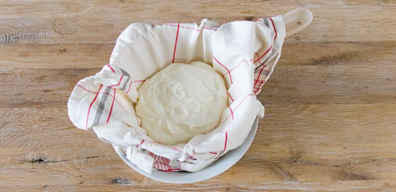 Joghurt im Sieb zur Abtrennung der Molke