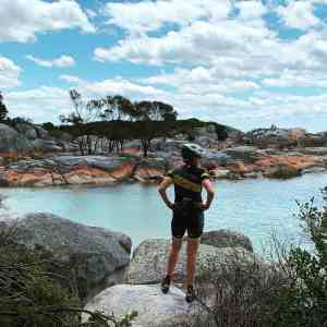 Bike rider standing in front of Bay of Fires