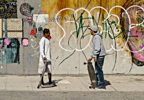 two teenagers conversing on the venice boardwalk with skateboards