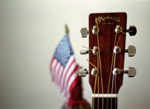 an acoustic Martin guitar posing with an american flag in the background