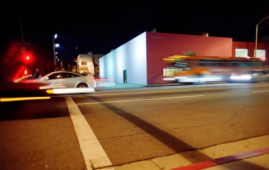 blurred cars and busses rush by a street corner at night in color
