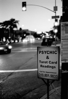 a sign on the street corner touting psychic readings in black and white