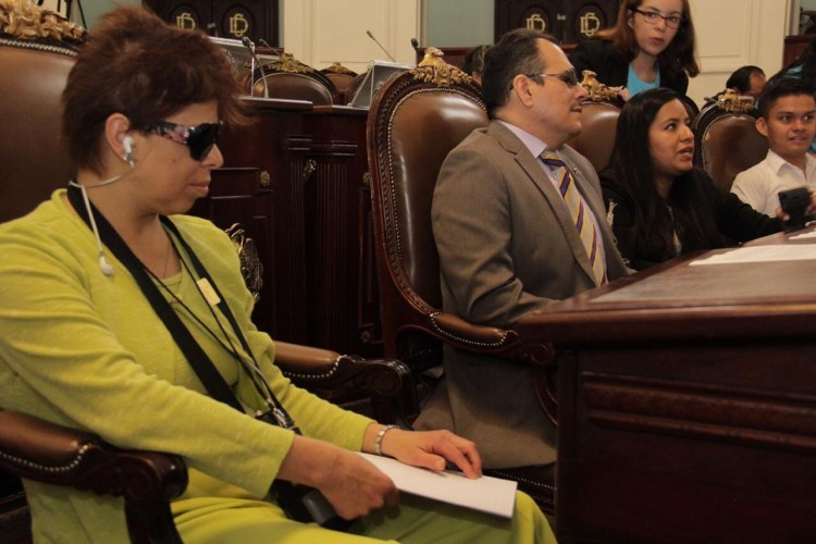 Sentados en el recinto legislativo, una mujer y un hombre ciegos