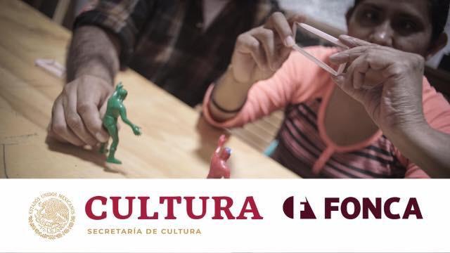 Cartel con los logos de Cultura y Fonca, en el centro se ven las manos de dos personas, una con un pequeño muñeco de plástico y otra sujetando la figura de un rectángulo.
