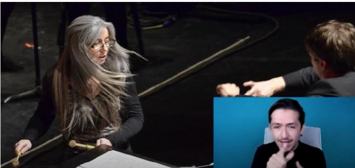 Se ve el rostro de Evelyn Glennie girando hacia un lado moviendo su cabello largo cano, mientras toca percusiones en una orquesta. Tomada del video de la entrevista Enseñar al mundo a escuchar