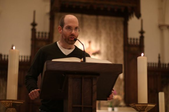 Mike stands at a pulpit in a church, speaking into a microphone, with a large book in front of him.