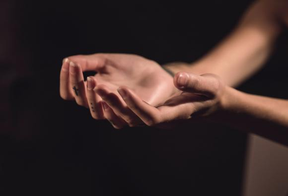 two hands, held palm up as if in prayer.  A small tattoo of a cross is visible on one finger.