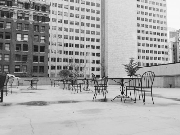 Empty cafe tables and chairs sit in a deserted courtyard surrounded by high-rise buildings.