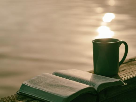 A bible and mig sit on a wooden railing beside a lake at sunset.