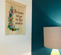 "An embroidered wall hanging that says ""Bis hierher hat uns der Herr geholfen!"" is hanging on a white wall, beside a teal wall. A lamp stands nearby."