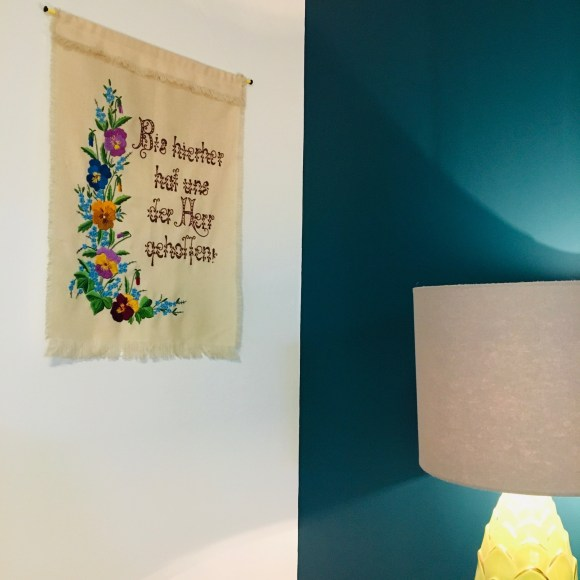 """An embroidered wall hanging that says """"Bis hierher hat uns der Herr geholfen!""""  is hanging on a white wall, beside a teal wall.  A lamp stands nearby."""