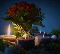 One candle is lit beside three unlit candles. There is greenery around the candles and a bouquet of flowers in the background.