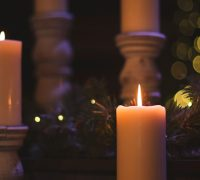 Two lit candles sit in front of evergreen branches. Two more unlit candles are in the background.