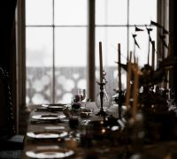 A table is set for a banquet in a dimly lit room. There are plates and silverware, and candles down the centre. There is a window in the background but no people are visible.