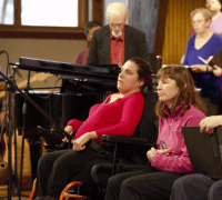 Chantal is sitting in the midst of a choir. She is a white woman with brown hair pulled back into a ponytail. She is wearing a red shirt and black pants and she is sitting in a motorized wheelchair. She is facing the choir conductor.