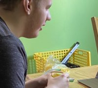 Logan is a young man, sitting at a table, using his tablet to participate in an online church service.