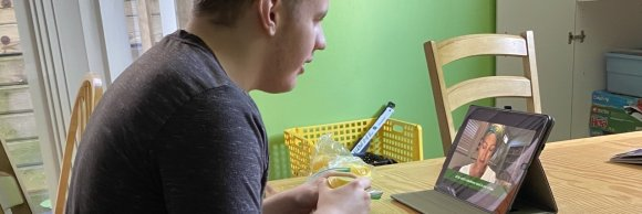 Logan is a young man, sitting at a table participating in an online church service using his tablet.