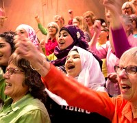 A group of people sing and are raising their hands in the air. Most of them are women. They are dressed in bright colours. A few women wear hijabs. There are people of various races and ages included.