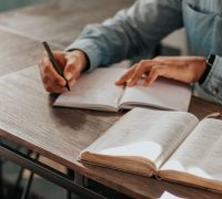 someone's hands are shown taking notes at a table with an open Bible beside them.