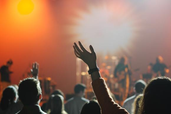 People are shown in a church worship service with their hands raised in the air.  A band is seen in the background, on stage.
