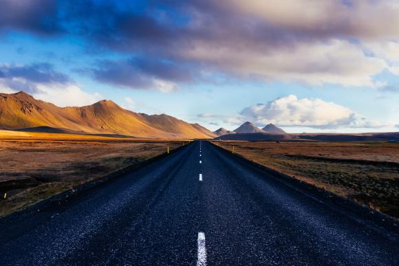 Prepare the road: An open highway stretches directly ahead into the distance. The road is paved and smooth. There are mountains in the distance beside the road. The sky is blue with clouds overhead.