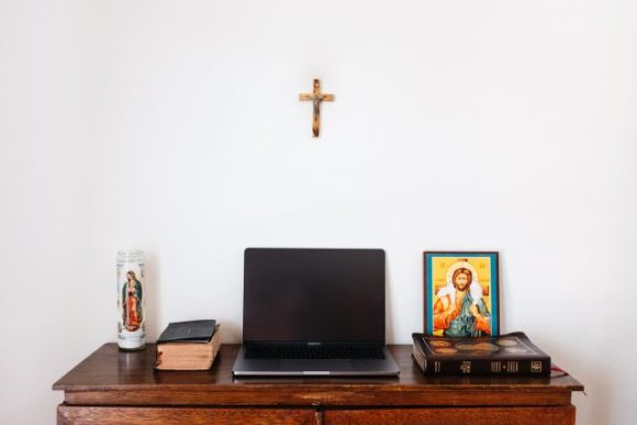an open laptop sitting on a desk surrounded by a bible, prayer books, and religious icons.