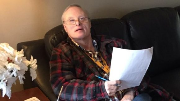 A man with Down syndrome and grey hair is sitting on a couch and looks up at the camera