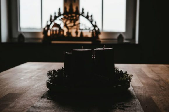 An advent wreath sits on a table.  The candles are unlit and it is in shadow.  In the background is a nativity scene.