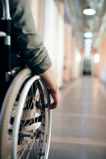A close-up photo shows a person's hand on their wheelchair wheel as if to start moving.  A long corridor stretches out ahead of them.