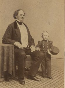 Photo portrait of George Washington Morrison Nutt standing with his hand on P.T Barnum's knee, 1862. Barnum is sitting, Nutt is not quite as tall as the bend in Barnum's elbow. Courtesy Barnum Museum