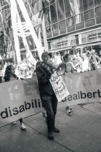 Man with megaphone leading disability pride parade