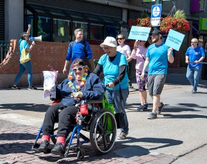 Woman in wheelchair being pushed by someone. Both people have big smiles.